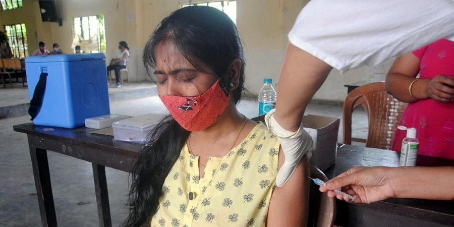 A beneficiary reacts while getting a dose of COVID-19 vaccine at SB Deorah College, in Guwahati