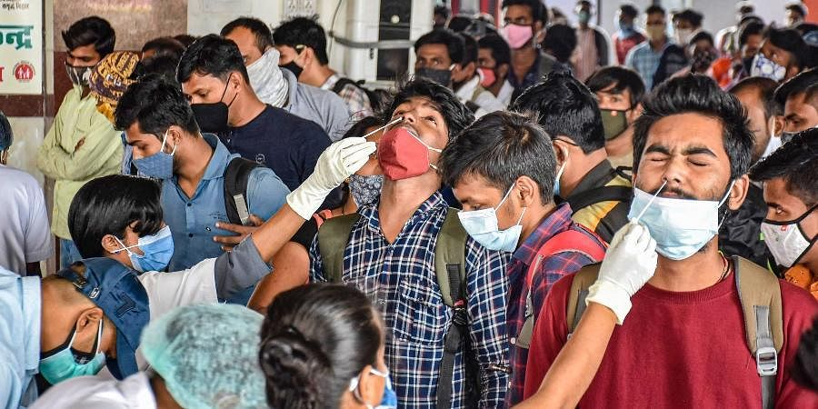Health workers collect swab samples of the passengers arriving from Maharashtra at a COVID-19 testing counter at Patna railway station, Wednesday,