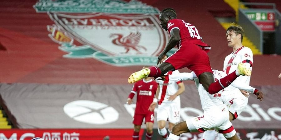 Liverpool's Sadio Mane, front, scores his side's opening goal during the English Premier League soccer match between Liverpool and Southampton