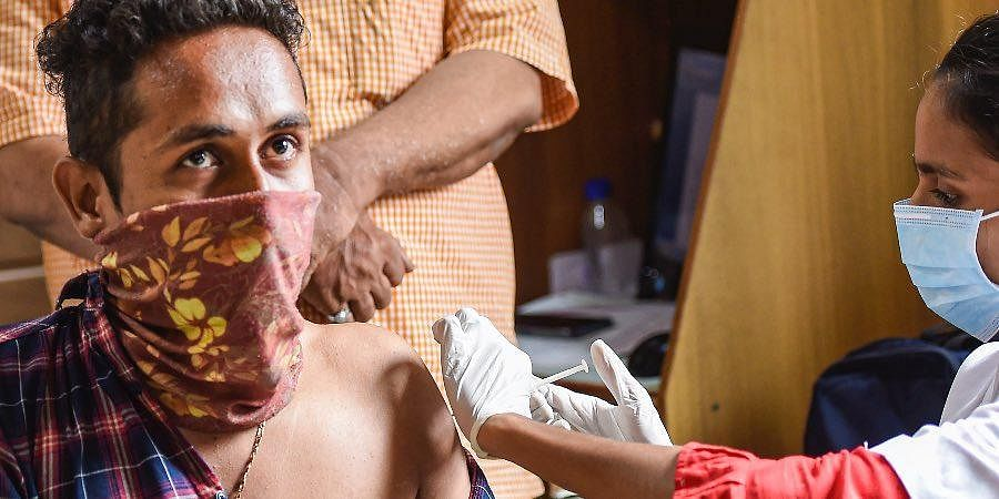 A vegetable vendor receives a dose of COVID-19 vaccine