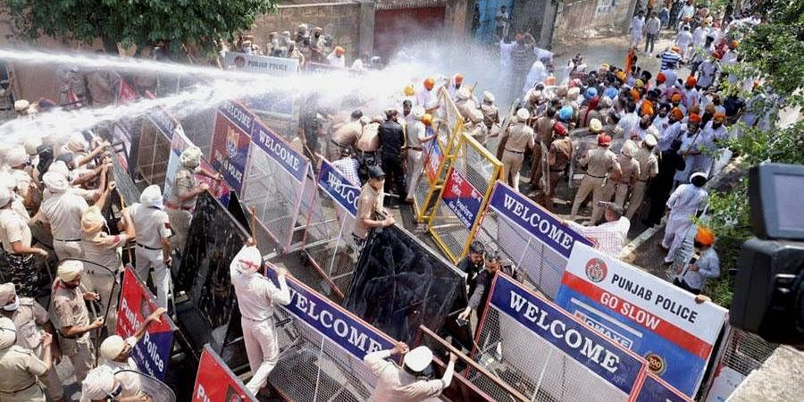 SAD & BSP workers hit by a water cannon during their protest demanding arrest of Health Minister Balbir Singh