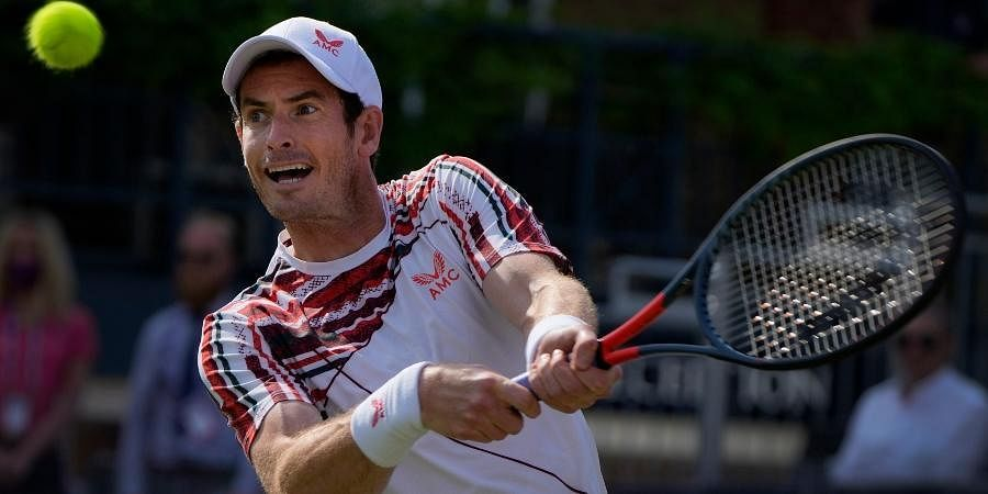 Andy Murray plays a return to Benoit Paire during their singles tennis match at the Queens Club tournament in London.