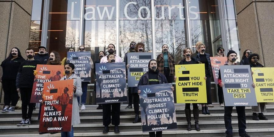 Greenpeace supporters demonstrate outside the Federal Court in Sydney,