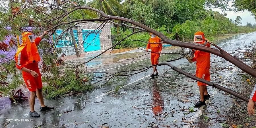 NDRF personnel clear a fallen tree from a road as they carry out restoration works following the landfall process of Cyclone Tauktae, in Valsad, Gujarat.