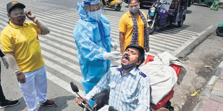 A medic collects a swab sample from a man for Covid-19 testing in New Delhi