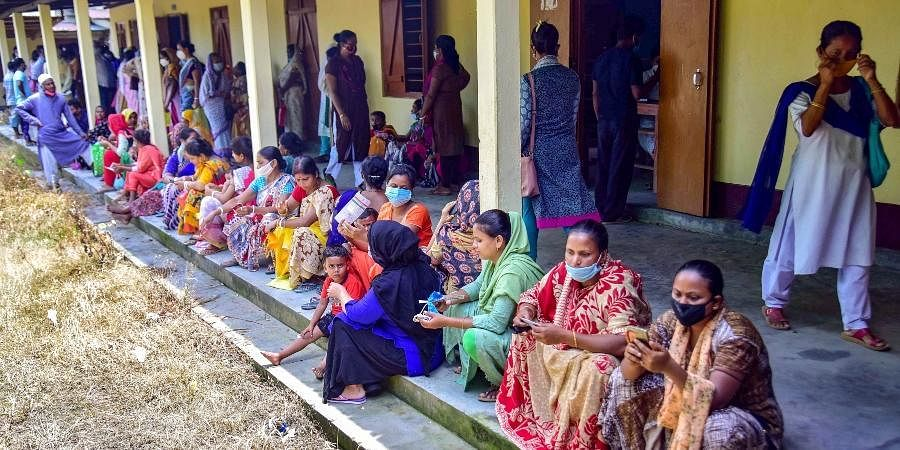 Beneficiaries wait in a queue to receive COVID-19 vaccine dose, at a centre in Nagaon district of Assam
