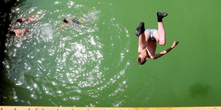 In this file photograph taken on June 25, 2019, youth jump into a canal near Reims, north-eastern France, as temperatures soar. (Photo   AFP)