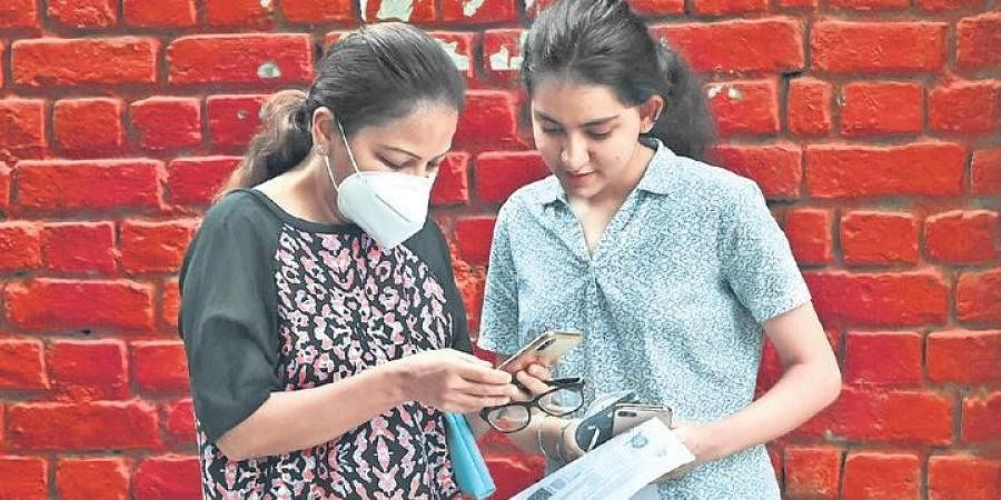 Students check their markets on a mobile phone after the CBSE declared Class X examination results on Wednesday (Photo | EPS)