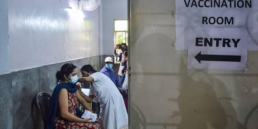 A health worker administers a dose of the COVID-19 vaccine to a woman, at a vaccination centre.