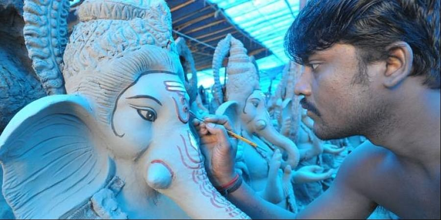 An Indian artist works on eco-friendly figures of Hindu deity Ganesha at a blue tarp-covered workshop on the outskirts of Hyderabad. The statues of eco-friendly clay Ganesh idols made with mud, jute and bamboo are aimed at reducing pollution during the Ganesh immersion. The popular eleven-day long Hindu religious festival, Ganesh Chaturthi will be celebrated from August 25 to September 5th of this year.