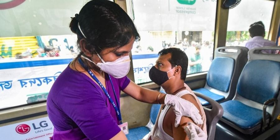 A medic administers a dose of COVID-19 vaccine to a man during 'vaccination on wheels' drive organised by Kolkata Municipal Corporation, at Posta wholesale market, in Kolkata. (Photo   PTI)