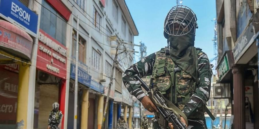 CRPF personnel stand guard on a street during restrictions imposed in the wake of the first anniversary of Article 370 abrogation in Srinagar Wednesday