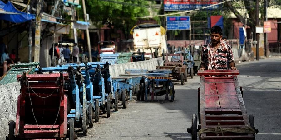 A worker pushes a handcart during the lockdown imposed amid the rise in COVID-19 cases in New Delhi