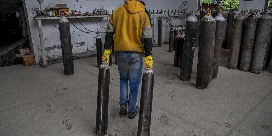 A worker moves empty oxygen cylinders for refilling at a gas supplier facility in Srinagar