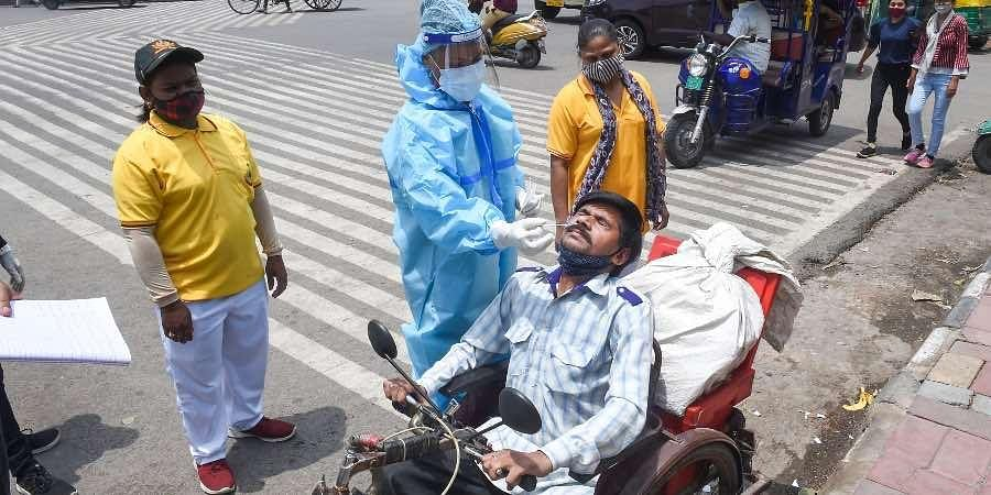 A medic collects a swab sample from a man for Covid-19 testing, in New Delhi