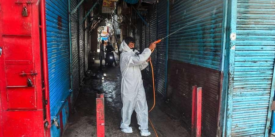 A worker sanitizes at Sadar Bazaar market area ahead of its reopening, as part of government's order of gradual unlocking of COVID-induced restrictions, in New Delh
