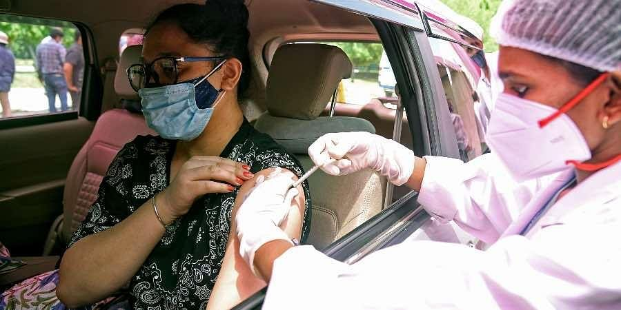 A medic inoculates the dose of the COVID19 vaccine during a drive-in vaccination.