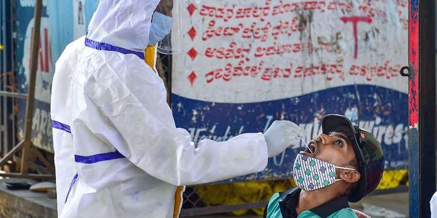 A health worker collects swab sample from a person for COVID-19 test, at a market in Bengaluru