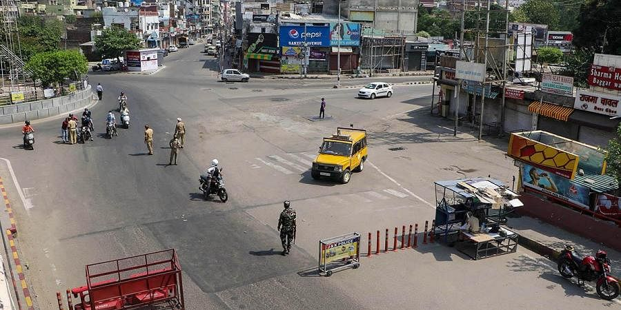 Security personnel check people during curfew imposed to prevent the spread of COVID-19 , in Jammu