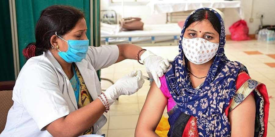 A beneficiary receives a dose of COVID-19 vaccine at a railway station in Prayagraj