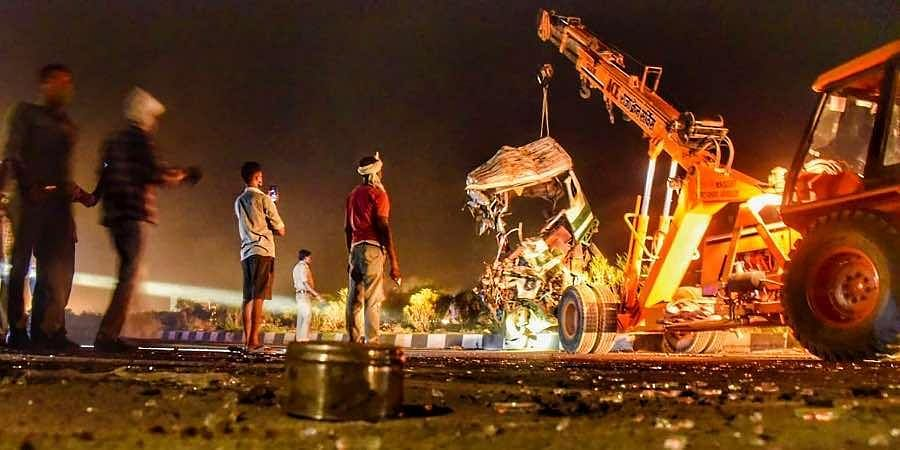 A crane lifts a bus crushed after it collided with a tempo truck, late night in Kanpur