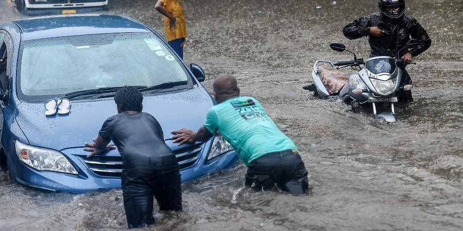 Two men try to push the vehicle as it stopped working due to a waterlogged road during heavy rain, at Kings Circle, in Mumbai, Wednesday, June 9, 2021.