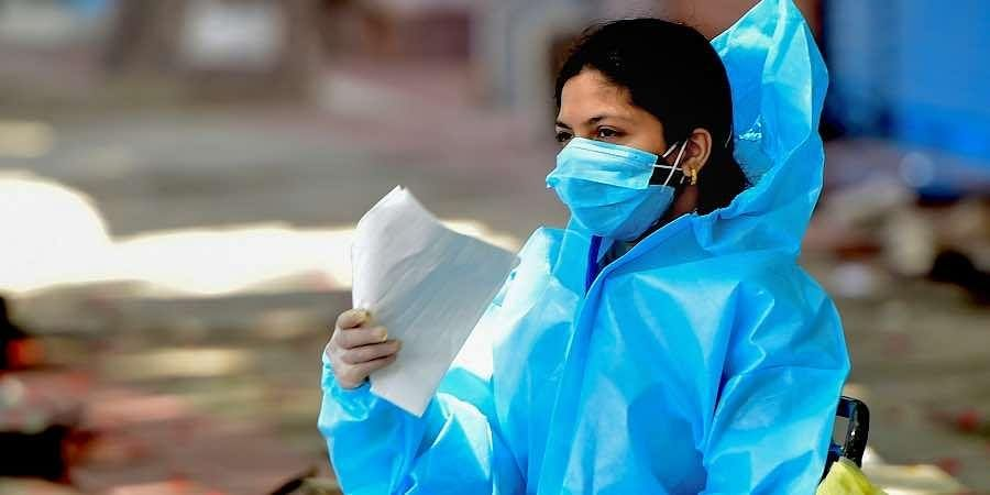 A health worker waits to conduct COVID-19 test, in Bengaluru