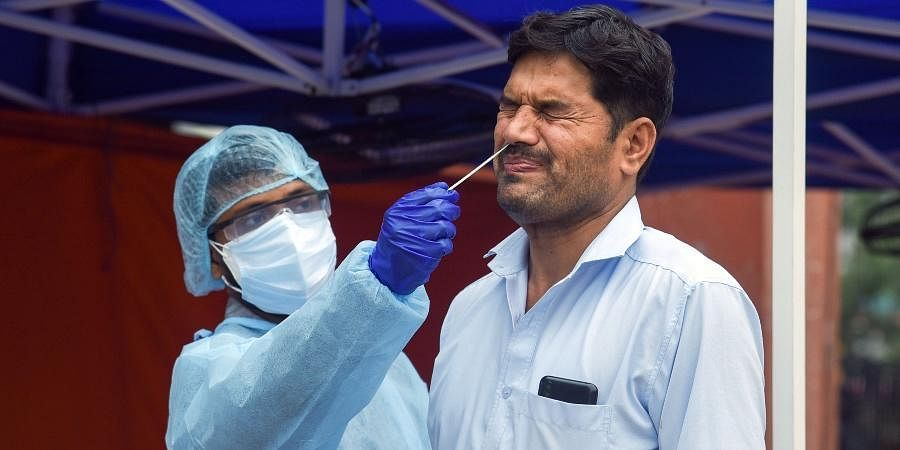 A health worker in PPE takes swab samples of a man for RT PCR COVID19 test, in New Delhi