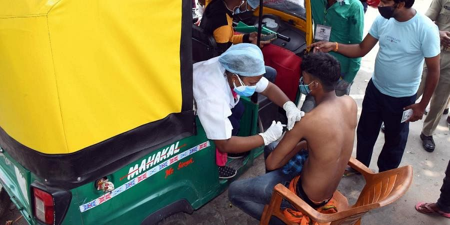 A medic inoculates the dose of COVID-19 vaccine to an auto-rickshaw driver in Ranchi