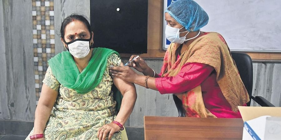 A health worker gives Covid vaccine to a woman.