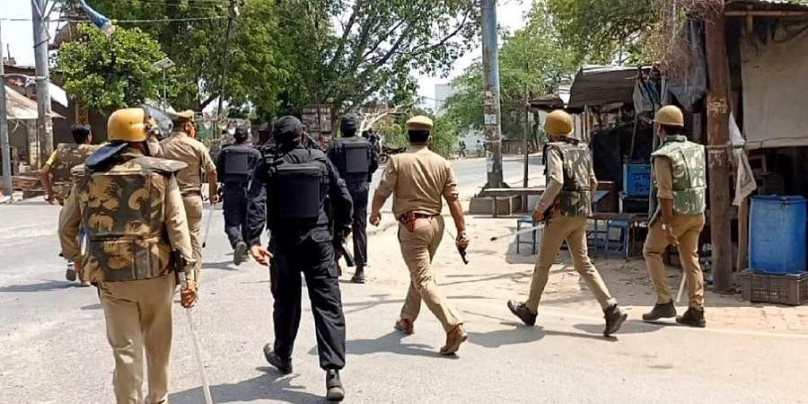 Police personnel in action after violence erupted during the block panchayat chief polling, in Etawah