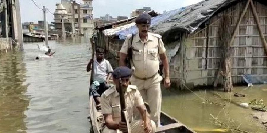 Policemen row a boat to the police station in Bihar's Ahiyapur