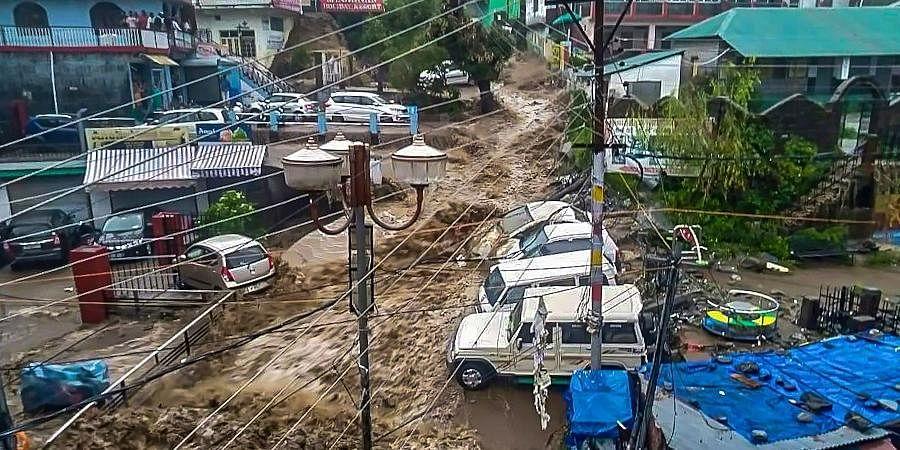 Flood water surges through a street amid heavy rain after a cloudburst, at Mcleodganj near Dharamshala