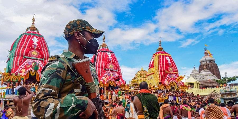 A police person stands guard during the annual Rath Yatra festival in Puri