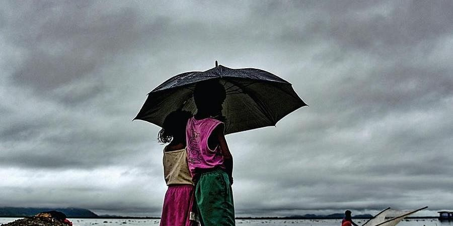 Children stand under an umbrella on the bank of Brahmaputra river during a rainy day, in Guwahati.