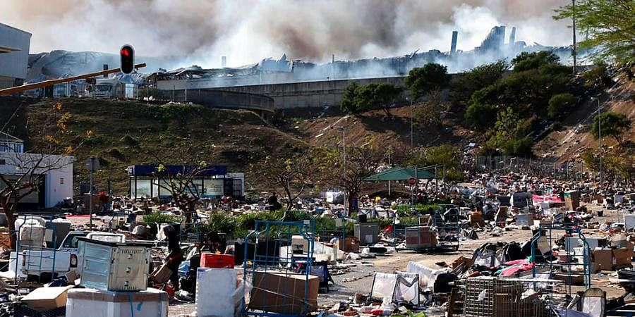 A factory burns in the background while empty boxes litter the foreground from looted goods being removed, on the outskirts of Durban, South Africa, Wednesday, July 14, 2021