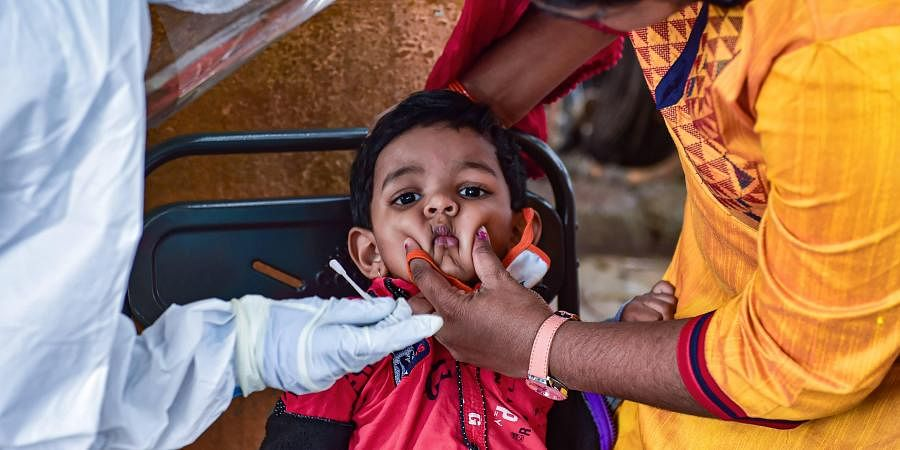 A health worker collects swab sample of a child for Covid-19 test. (Photo | PTI)