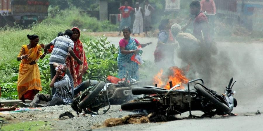 People injured in poll violence sit by the side of a road as a vehicle is set on fire by locals during Panchayat polls in Nadia district of West Bengal.