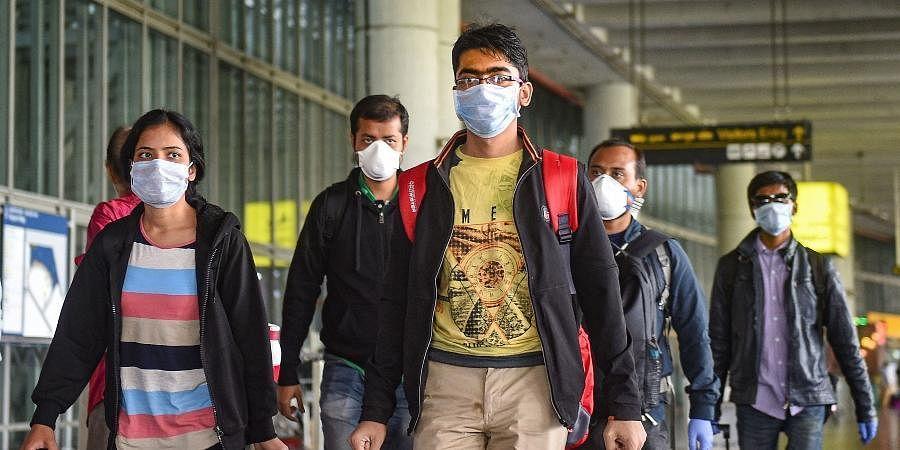 Passengers wear masks in the wake of coronavirus pandemic at the Kolkata airport