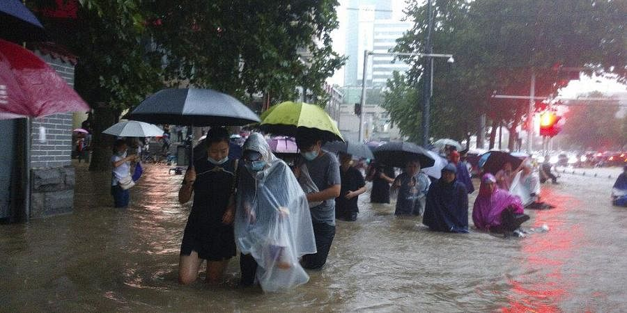 People move through flood water after a heavy downpour in Zhengzhou city, central China's Henan province on Tuesday, July 20, 2021. (Photo | AP)