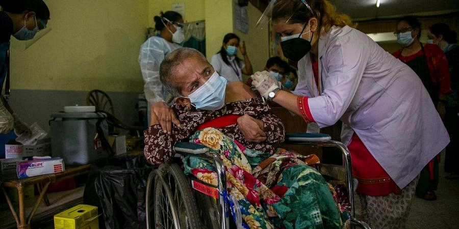 An elderly physically disabled Nepalese woman receives a dose of Johnson and Johnson vaccine at the Nepal Disabled Association Khagendra New Life Center in Kathmandu