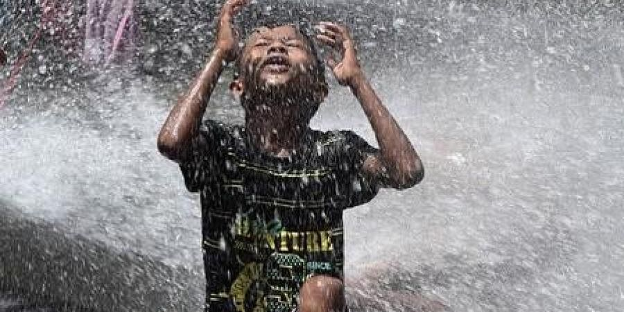 A boy cools himself from a water pipe during a hot summer afternoon as mercury level increases in the capital on Friday.
