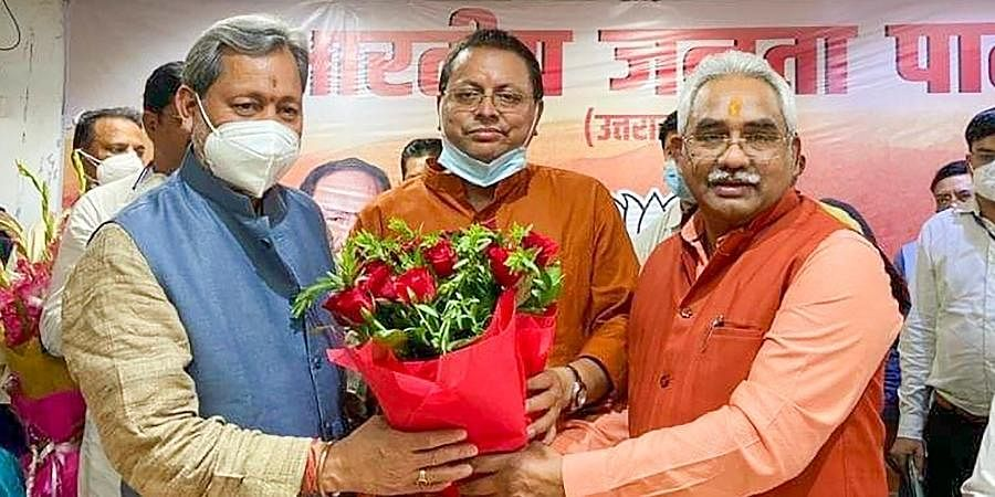 Newly elected Uttarakhand CM Pushkar Singh Dhami (C) with former CM TS Rawat and BJP state President Madan Kaushik, in Dehradun. (
