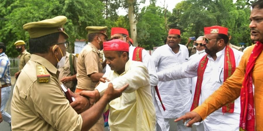 SP leaders and supporters stage a protest over alleged adoption of unfair methods during the Zila Parishad Chairperson election, in Aligarh, Saturday, July 3, 2021.