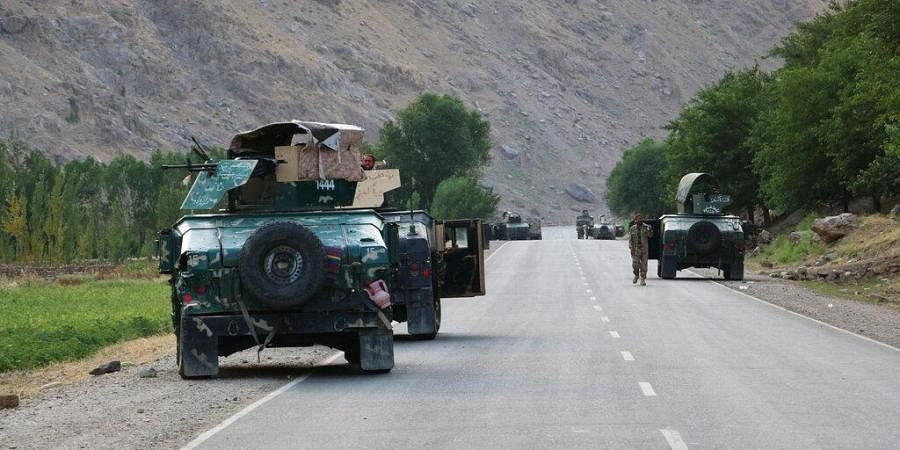 Afghan soldiers pause on a road at the front line of fighting between Taliban and Security forces, near the city of Badakhshan