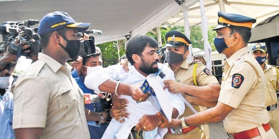 BJP legislator Ram Satpute is taken away by policemen during the stormy opening day of  Maharashtra Assembly, in Mumbai.