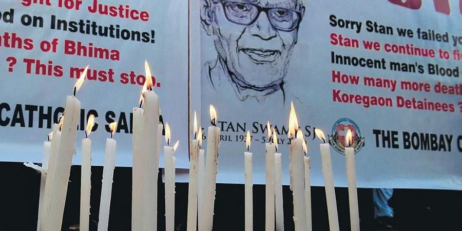 People hold posters next to candles outside a church holding memorial mass for Stan Swamy in Mumbai.
