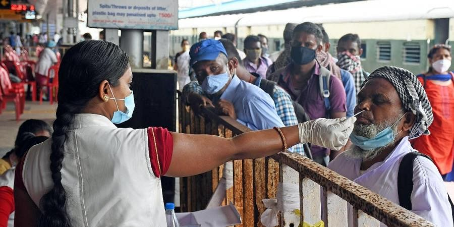 A healthcare worker collects a nasal sample for the COVID-19 test at Ranchi railway station